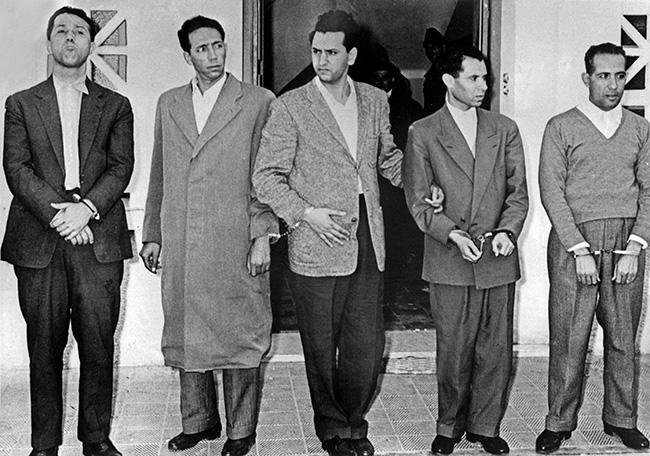 Photo de groupe des chefs historiques algériens du Front de Libération National (FLN), menottes aux poignets devant les locaux de la DST à Alger le 22 octobre 1956 après l'arraisonnement au-dessus de l'Algérie de l'avion qui les conduisait de Rabat à Tunis : (de G à D) Ahmed Ben Bella, Mohammed Boudiaf, Hocine Aït Ahmed, Mustapha Lacheraf et Mohamed Khider (Jacques GREVIN / AFP)