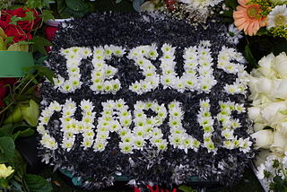 """Couronne mortuaire Je suis Charlie, sur la tombe de Tignous - <a href=""""https://commons.wikimedia.org/wiki/File:Je_suis_Charlie,_couronne_de_fleurs_sur_la_tombe_de_Tignous,_le_jour_de_son_enterrement.jpg"""">image</a>, sous <a href=""""http://creativecommons.org/licenses/by-sa/3.0/deed.fr"""">licence CC</a>"""
