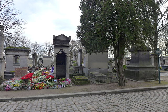 """Tombe de Tignous, le jour de son enterrement - <a href=""""https://commons.wikimedia.org/wiki/File:Tombe_de_Tignous_le_jour_de_son_enterrement.jpg"""">Image</a> Perline, sous <a href=""""http://creativecommons.org/licenses/by-sa/3.0/deed.fr"""">licence CC</a>."""
